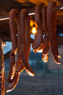 Hecha, Ukraine - JAN 27, 2018: Pork butchers completion. Smoke-dried  sausages hang on the bar. tasty traditional food