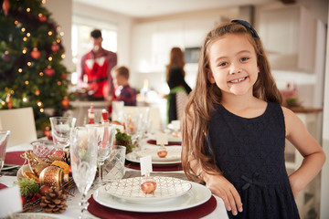 Portrait Of Daughter Helping To Lay Table As Family Prepare For Christmas Meal At Home