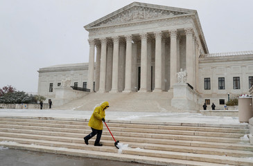 A worker clears snow from the steps outside of the U.S. Supreme Court in Washington