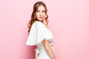 Happy business woman standing and smiling isolated on pink studio background. Beautiful female half-length portrait. Young emotional woman. The human emotions, facial expression concept