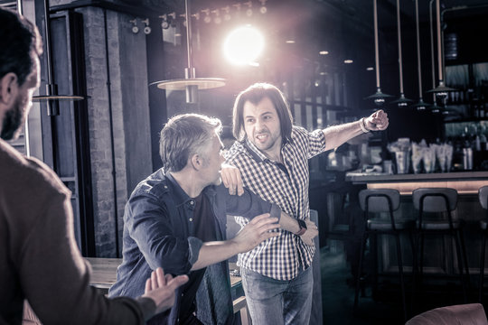 Angry two males having quarrel in pub
