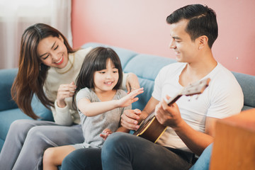 Happy Cheerful smiling Young Family mother father and daughter sitting on the blue sofa, father and daughter play a guitar, rose pink color background wall