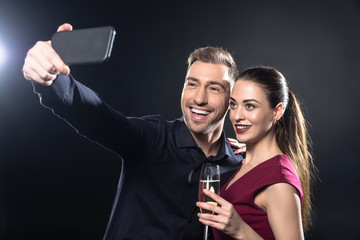 happy young couple taking selfie with smartphone during party on black