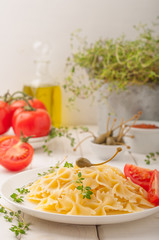 Farfalle pasta with tomatoes, capers, basil, thyme, olive oil and tomato sauce. Pasta on a plate on white wooden background