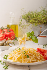 Farfalle pasta with tomatoes, capers, basil, thyme and tomato sauce. Pasta on a plate on white wooden background. A fork with pasta.