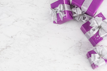 Christmas purple gifts with silver ribbon on marble table