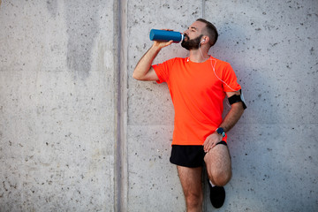 Man resting from running and drinking water while standing against the wall. Healthy lifestyle concept.