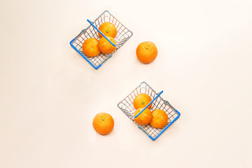 fresh arabic groupe of mandarin fruits in  metal shopping basket isolated on pink background