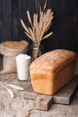 Wholegrain bread. Unleavened wheat  bread on a cutting board with flour, wheat grains, spikelets on a wooden brown table. A loaf (brick) of bread. Dark background. Homemade.