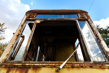 Old rusty destroyed tram outdoors at sunny day.