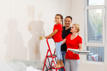 Happy family mother father and child daughter are doing repairs paint wall at home