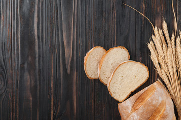 Bread. Loafs of white wheat bread, sliced on a brown wooden table with a bag of wheat grains and wheat spikelets. Top view. Copy space. Rustic.