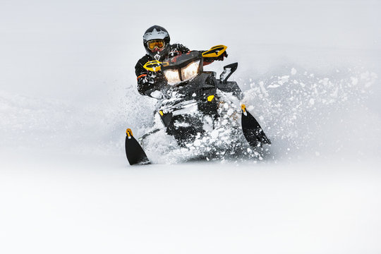 In deep snowdrift snowmobile rider make fast turn. Riding with fun in deep snow powder during backcountry tour. Extreme sport adventure, outdoor activity during winter holiday on ski mountain resort.