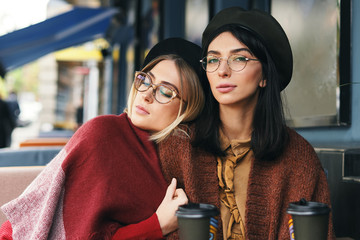 Portrait of two young women in an outdoor cafe, drinking coffee