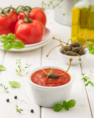 Caper and tomato sauce in a white bowl on white table with basil and thyme