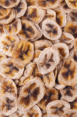 Dried banana slices (chips) background. Dehydrated crispy fruit slices. Heap, pile of sun dried crunchy bananas.