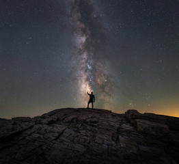 A silhouette of a man reaching for the stars of the Milky Way Galaxy