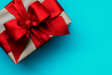 Gift box with red ribbon on turquoise background