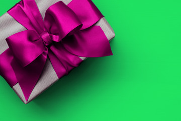 Gift box with pink ribbon on green background