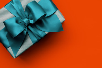 Gift box with turquoise ribbon on orange background