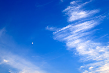 Beautiful picturesque white feather clouds on the dark blue sky with a young moon , magic romantic background