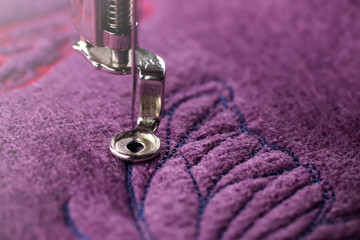 embroidery of blue butterfly on purple boiled wool - detailed close up on stitching area
