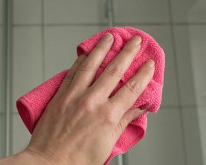 Hand beim reinigen einer Duschkabine