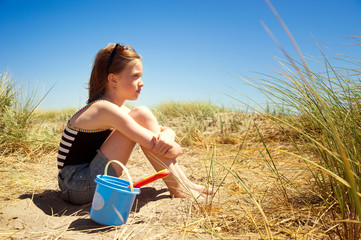 Girl with toys sitting on sand against clear sky