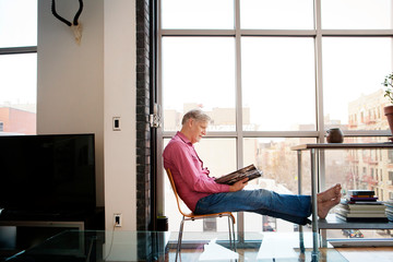 Side view of man reading book while sitting on chair at home