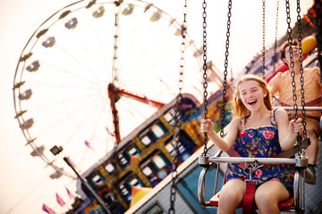 Cheerful couple enjoying in chain swing ride at amusement park