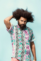 Portrait of hipster with curly hair standing against blue background
