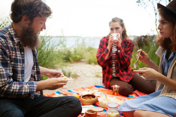 Friends having breakfast while sitting on field against sky