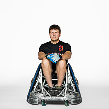 Portrait of man sitting on wheelchair against white background