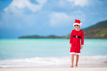 Adorable little girl in Santa hat on tropical beach
