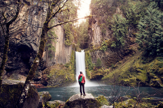 Woman looking at waterfall while standing on rock in forest