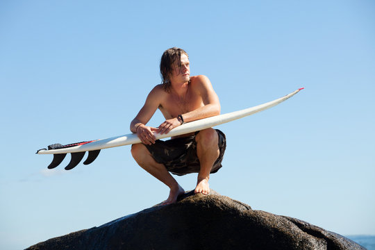 Man with surfboard looking away while crouching on rock
