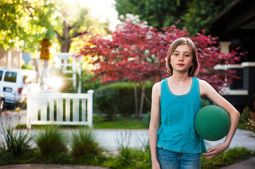Portrait of girl with ball standing in lawn