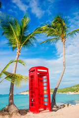 Beautiful landscape with a classic phone booth on the white sandy beach in Antigua