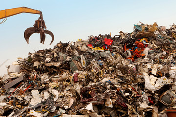 Cropped image of crane over garbage heap at junkyard
