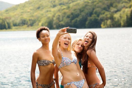 Happy female friends clicking selfie against lake
