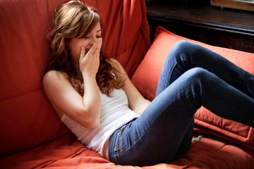 Happy woman sitting on sofa at home
