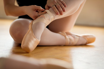 Low section of woman lacing up ballet flats while sitting in studio