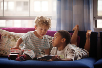 Boy holding tablet while looking at brother at home