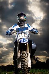 Full length portrait of confident dirt biker against cloudy sky