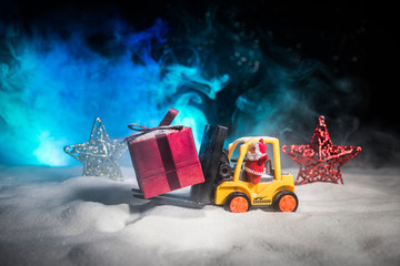 Miniature Gift Box by Forklift Machine on snow ,Determined Image for Christmas Holiday and Happy New Year Gift Celebration concept.