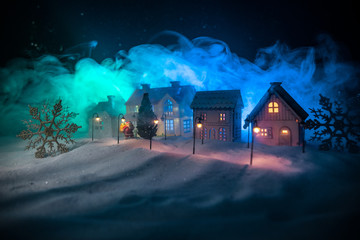 Little decorative houses, beautiful festive still life, cute small houses at night, Night city real bokeh background, happy winter holidays. Selective focus