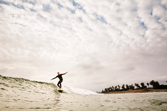 Man with arms outstretched surfboarding against cloudy sky