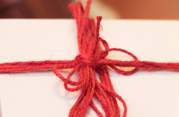 Close-up: white box with a gift is well tied with red tape. Concept: time to give and receive gifts.