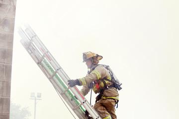 Firefighter climbing ladder against sky