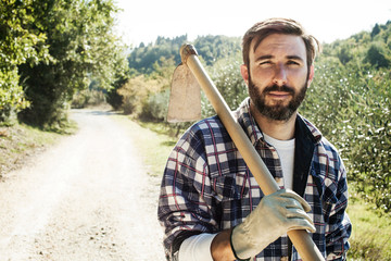 Portrait of man carrying garden hoe while walking on road